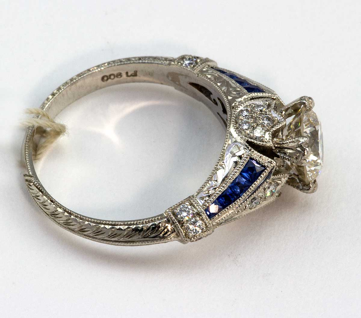 Platinum ring center stone weighs 1.25 SI1 and H color, with sapphires and diamonds on band